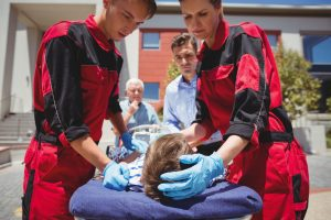 Paramedics examining injured boy on street